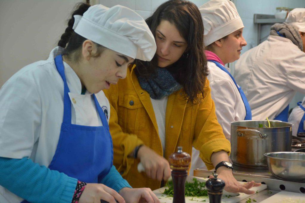 Joven con uniforme de cocina, cortando verduras sobre un mesón, acompañado por una operadora laboral