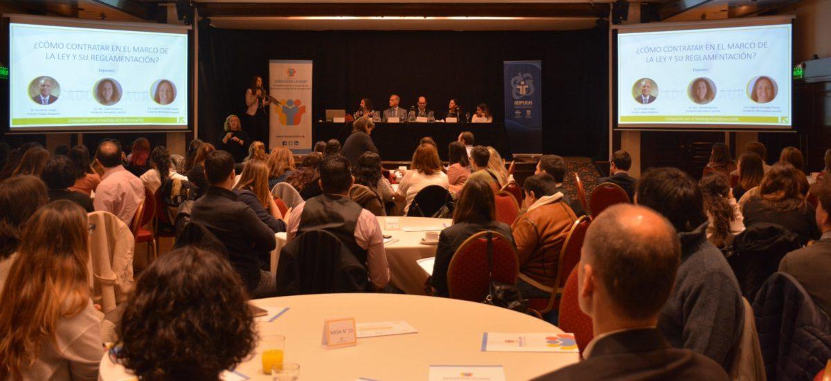 Plano abierto que muestra a un grupo de personas sentadas en mesas. Y de fondo, un panel de expositores conversando.