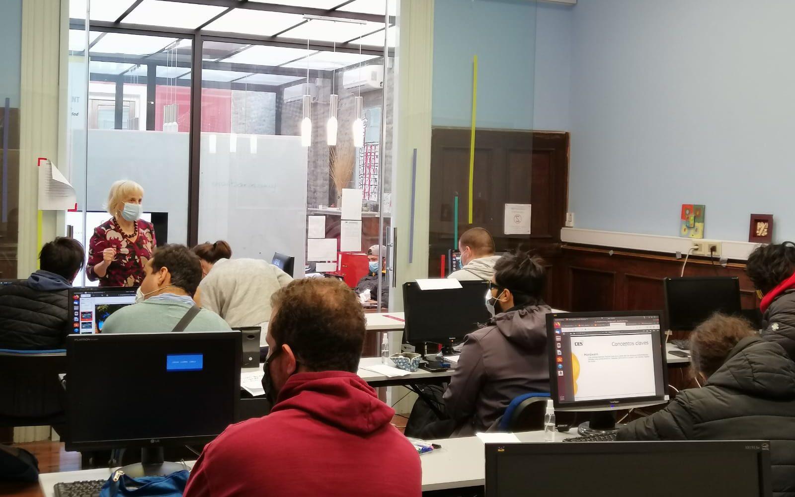 Imagen que contiene interior de salón de clases con estudiantes sentados frente a computadores.