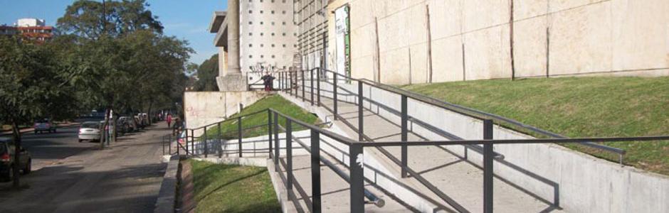 Imagen que muestra rampa exterior de acceso en facultad de arquitectura de UdelaR para desplazamiento de personas con discapacidad.