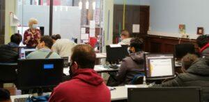 Jóvenes sentados en largas mesas con computadores escuchando a una docente hablar en un salón de clases