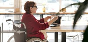 Mujer usuaria de silla de ruedas en un computador, en una cafetería