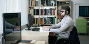 Persona ciega sentada en oficina, usa lentes oscuros y auriculares y lee.